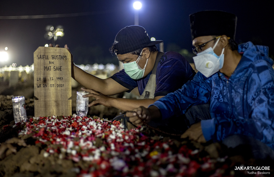 A family of the deceased pray next to the grave at Rorotan Cemetery in Cilincing, North Jakarta, on July 23, 2021. (JG Photo/Yudha Baskoro)