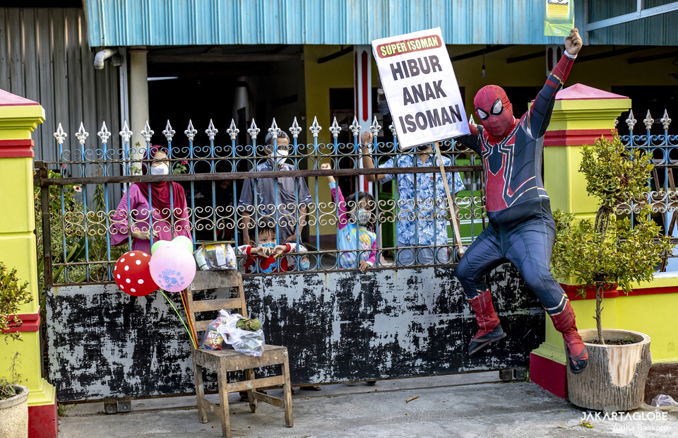 Super Isoman jumps as he tries to amuse children during self-isolation at Sukoharjo, Central Java on July 31, 2021. (JG Photo/Yudha Baskoro)
