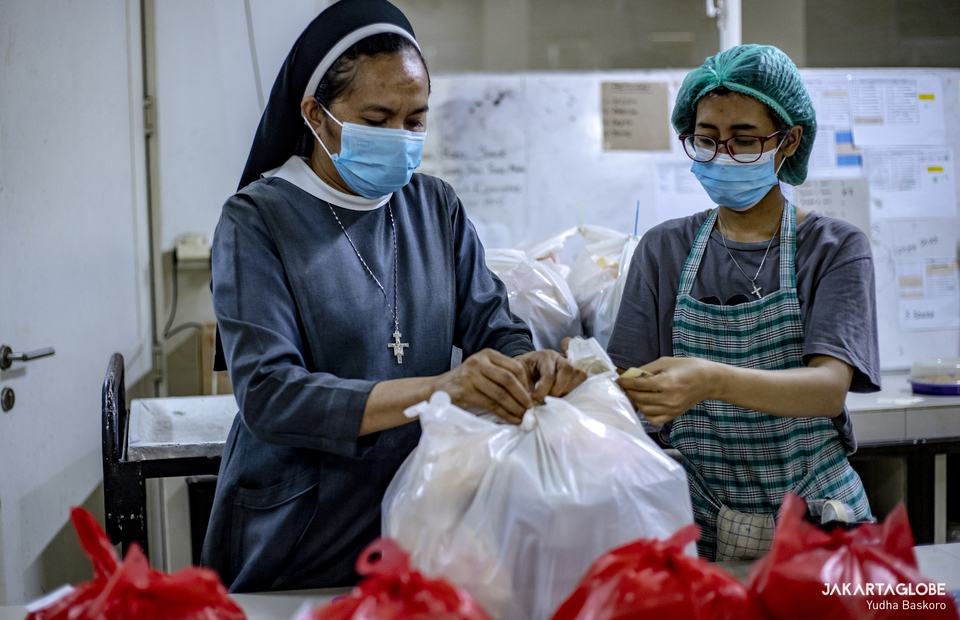 A nun and a worker prepare food inside a kitchen at Samadi Pastoral Centre in East Jakarta on August 5, 2021. (JG Photo/Yudha Baskoro)