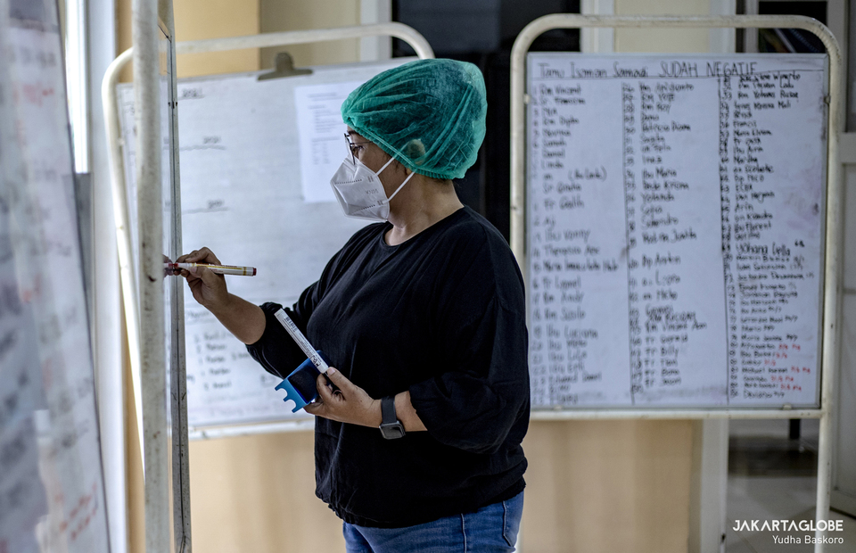 A worker writes in a whiteboard about how much patient positive and undergoing treatment at Samadi Pastoral Centre in East Jakarta on August 5, 2021. (JG Photo/Yudha Baskoro)