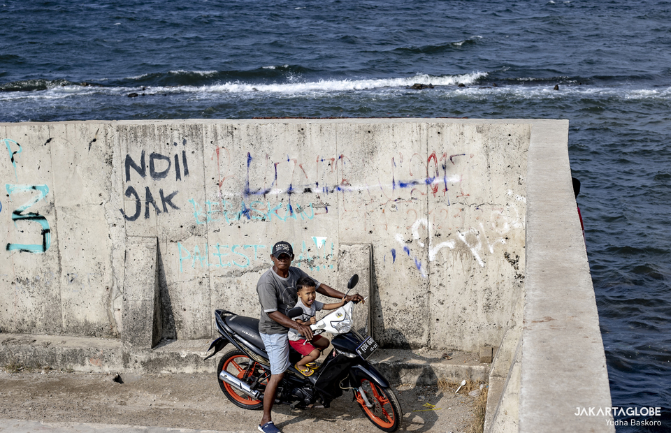 A man carries his child as they ride a motorcycle at Jakarta Giant Sea Wall in Muara Baru, North Jakarta on August 12, 2021. (JG Photo/Yudha Baskoro)
