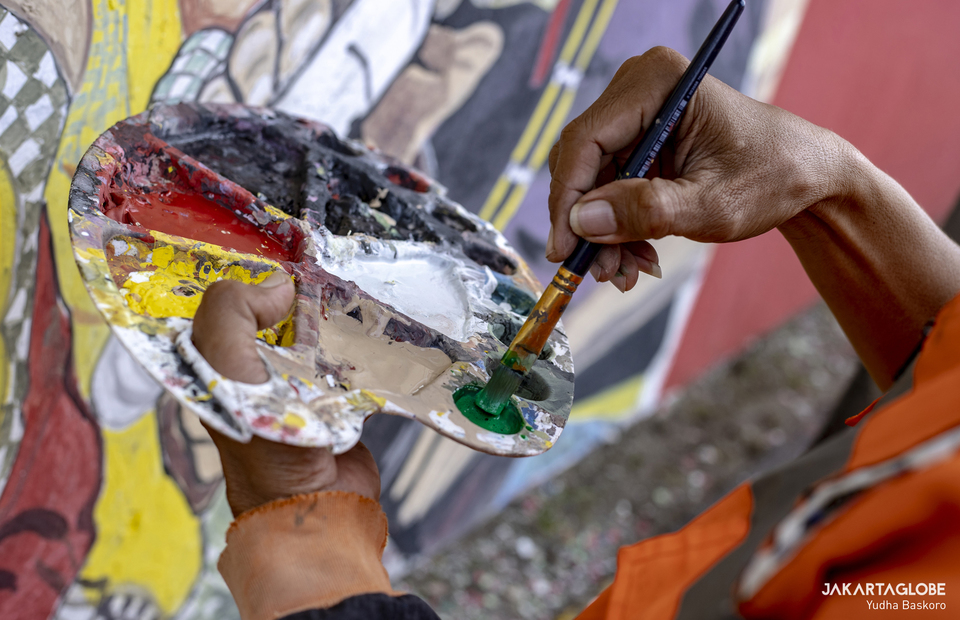 Gunawan uses a color palette to paint a mural at Tebet fly over in South Jakarta on August 15, 2021. (JG Photo/Yudha Baskoro)