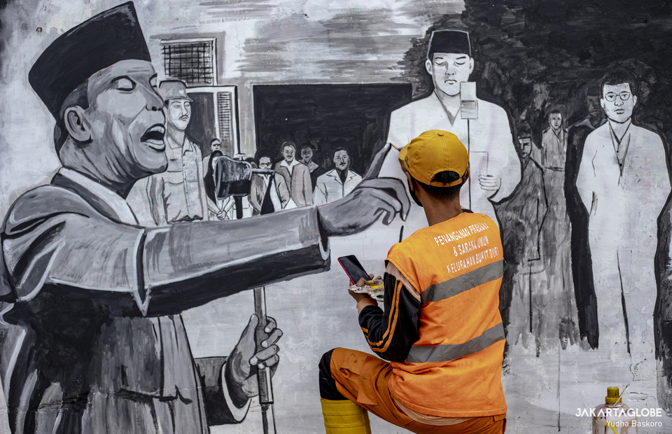 Gunawan paints a mural at Tebet fly over in South Jakarta on August 15, 2021. (JG Photo/Yudha Baskoro)