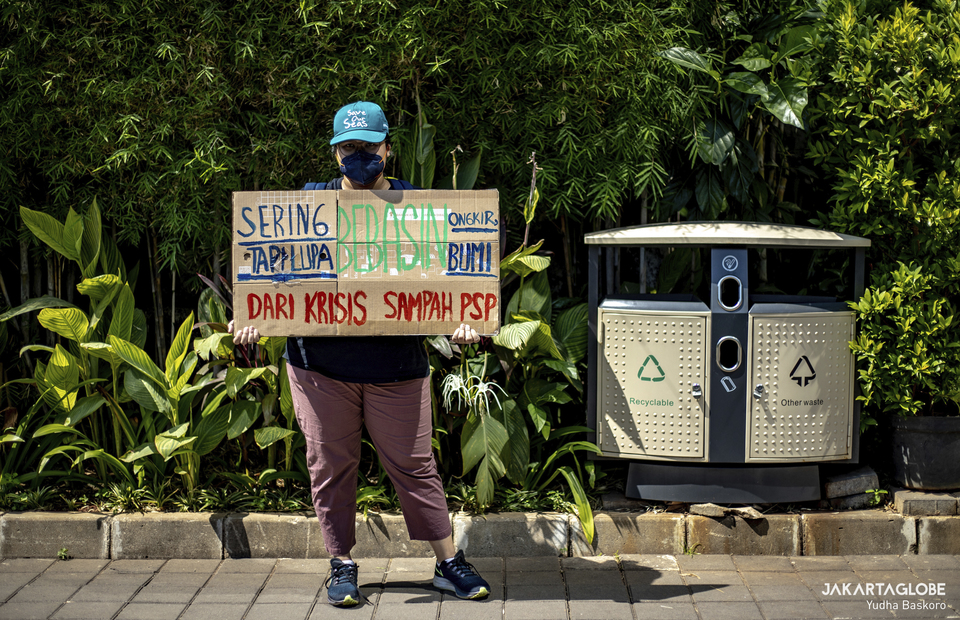 Protester carries a placard as she stands aside a recycle bin outside Tokopedia tower building in South Jakarta on September 9, 2021. (JG Photo/Yudha Baskoro)