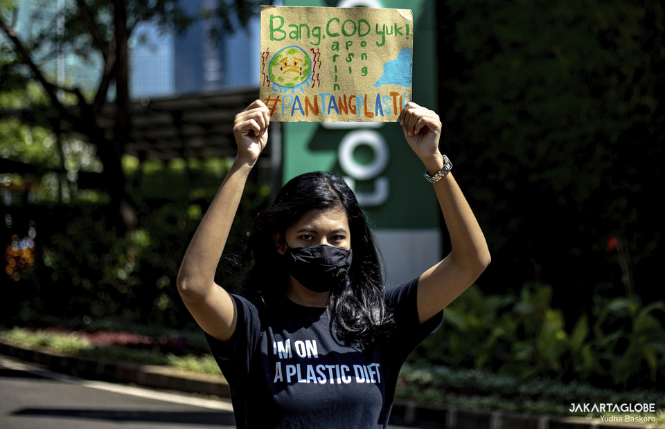 Protester carries placard outside Tokopedia tower building in South Jakarta on September 9, 2021. (JG Photo/Yudha Baskoro)