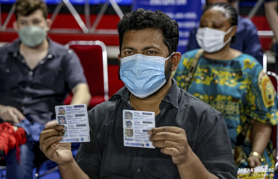 A man shows his family UNCHR identity card during a mass vaccination program for refugees and asylum seekers at Bulungan sports hall in South Jakarta on October 7, 2021. (JG Photo/Yudha Baskoro)