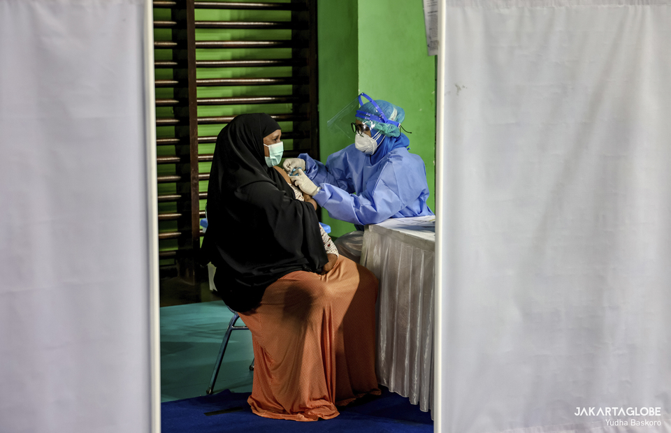 A woman receives her first dose of Covid-19 vaccine during a mass vaccination program for refugees and asylum seekers at Bulungan sports hall in South Jakarta on October 7, 2021. (JG Photo/Yudha Baskoro)