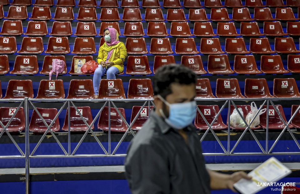 A woman sits in a tribune during a mass vaccination program for refugees and asylum seekers at Bulungan sports hall in South Jakarta on October 7, 2021. (JG Photo/Yudha Baskoro)